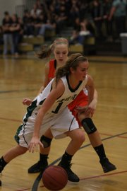 Free State sophomore Lynn Robinson (14) dribble past Shawnee Mission Northwest sophomore  Megan Musson (12) during the girls' varsity game Tuesday night at Free State High School. The Lady Firebirds lost to the Cougars 55-22..