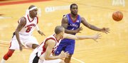 Kansas guard Sherron Collins dishes a pass as he is guarded by Nebraska defenders Sek Henry (5) and Ryan Anderson (44) during the first half Wednesday, Jan. 13, 2010 at the Devaney Center in Lincoln, Nebraska.