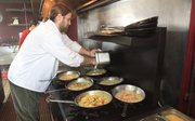 Chef Bradley Walters preps up a stove full of pasta dishes at The Basil Leaf Café, 3300 W. Sixth St.