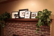 The mantel is re-decorated after the holidays with a simple collection of framed photos in black and white.