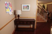 Laura Tiffany moves a hallway table, top, to a new location behind a couch to add display and storage space.
