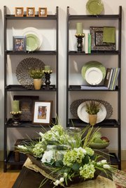 A pair of wall shelves create multiple areas to design and display collections of items including books, plates and candles.