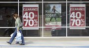 With purchases in hand, a shopper walks past a store advertising clearance sales Thursday in Tallahassee, Fla. Retail sales unexpectedly fell in December, leaving 2009 with the biggest yearly drop on record and highlighting the formidable hurdles facing the economy as it struggles to recover from the deepest recession in seven decades.