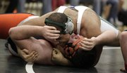 Free State senior wrestler Ammon Austin (top) pinned Justin Heindel in 285-weight class as the Firebirds hosted Shawnee Mission Northwest Wednesday, Jan. 20, 2010.