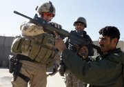 Canadian Police Constable Craig Dickie, left, from Milton, Ontario, demonstrates a gun to an Afghan police officer at a checkpoint in Kandahar City, southern Afghanistan, in this Jan. 17, 2010, file photo. U.S. and Canadian forces are operating on a tight deadline to train a police force that can obstruct a Taliban comeback in Kandahar, which is the place where the militant movement began in the early 1990s.
