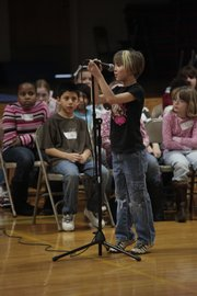 Lily Russell, third-grader at Kennedy school, steps up to the microphone to spell a word during the school's spelling bee Thursday, January 14, 2010.