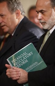 Federal Reserve Chairman Ben Bernanke, right, holds a copy of the outlined reforms as he sits next to Lawrence Summers, the director of the White House National Economic Council, in the East Room of the White House in Washington in this June 17, 2009, file photo.
