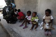 A girl cries after receiving food in an improvised distribution center organized by the United Nations as a U.N. peacekeeper from Brazil kneels to talk to children Sunday in the Cite Soleil neighborhood in Port-au-Prince, Haiti.