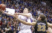 Kansas guard Brady Morningstar cuts to the bucket past Missouri forward Justin Safford during the first half, Monday, Jan. 25, 2010 at Allen Fieldhouse.