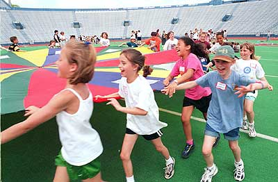 Centennial School third graders play games with a parachute during Kansas Kids Fitness Day at the Kansas University Memorial Stadium. The statewide event focused on non-competitive physical activity for third grade students. More than 500 Lawrence schoolchildren attended the event at KU.