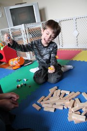 Max San Miguel, 6, topples a Jenga tower during a play therapy session. His therapist, Jamie Gabriel, says that Jenga helps Max be more deliberate with his thoughts and actions.
