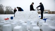 "Kansas University sophomore Daniel Siegel, left, Overland Park, watches as John Bergman, Lawrence sophomore; Kurtis Myers, Chanute sophomore; and Kevin Meyer, Lenexa junior, right, construct an igloo Friday in the open field next to Robinson Gymnasium on the KU campus. When asked about their motivation, Meyer replied, ""It was either this or video games."""