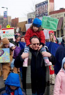 Jeremy Cooper carries Ava Cooper, 4, on his shoulders during a march down Mass Street on Saturday, Feb. 6, 2010.  The march was organized by Save Our Neighborhood Schools, an organization whose goal is to prevent the closing of Lawrence public schools.