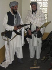 Qari Mohebulla Nakarar, left, and Fazel Rahman Farouqi, former pro-Taliban fighters, pose for a photograph while holding their newly surrendered Soviet-era weapons Jan. 31 at an Afghan government-run reconciliation office, in Jalalabad, Nangarhar province, east of Kabul, Afghanistan.