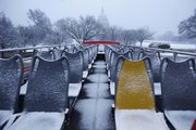 An empty open-top double-decker tour bus drives near the Capitol in Washington as snow fell Friday in the Washington area. Life in the nation's capital ground to a halt Friday as steady snow fell, the beginning of a storm that forecasters said could be the biggest in modern history.