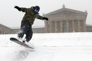 Mike Nagao snowboards down the snow-covered steps of the Philadelphia Museum of Art during a winter storm Saturday in Philadelphia.