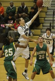 Free State's Evan Manning (32) scores two points against Mission defender's Brandon Stacker (25) and Alex Moyer (20). The Firebirds fell 35-42 to the Raiders Tuesday.