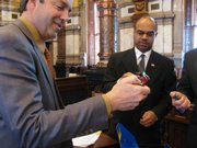 State Sens. Chris Steineger and David Haley, both Democrats from Kansas City, sample novelty cigarette lighters collected by state Sen. Oletha Faust-Goudeau, D-Wichita. The Senate on Thursday approved a bill to ban the lighters.