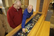 Hundreds of Jayhawks are on display at the Kansas Union, part of Bud Jennings' collection over a lifetime. Jennings, left, and Kansas Union director of marketing Mike Reid check on one of the display cases of small pieces.
