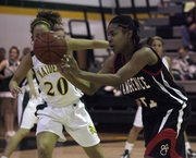 LHS junior Tamiya Green (right) gets the ball off Tuesday, Feb. 16, 2010 during the Lawrence and Shawnee Mission South girls game in Overland Park.