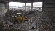 A front loader pushes giant mounds of residential curbside material on Friday after being unloaded at the Kansas City, Kan. facility. Deffenbaugh Industries has announced that they will offer weekly curbside recycling for Lawrence residents. Just a couple of weeks after the city commission said it was going to leave curbside recycling to private haulers, the largest recycling company in the region is jumping into the Lawrence market.