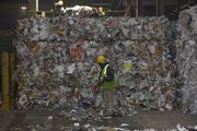 A worker sweeps loose paper near a wall of bundled bales of paper material at the Kansas City, Kan., recycling facility. Deffenbaugh Industries has announced that they will offer weekly curbside recycling for Lawrence residents. Just a couple of weeks after the city commission said it was going to leave curbside recycling to private haulers, the largest recycling company in the region is jumping into the Lawrence market.