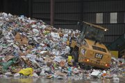 Giant mounds of residential recycling material is piled up after being unloaded at the Kansas City, Kan., Deffenbaugh Industries facility.