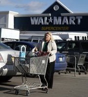 A shopper makes her way to her car Thursday at a Walmart in Brunswick, Maine. Wal-Mart Stores Inc., one of the recession's biggest beneficiaries, felt the pinch during the fourth quarter as quarterly sales fell at U.S. Wal-Mart stores for the first time.