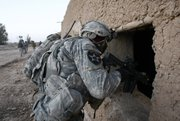 A U.S. soldier of the 1st Battalion, 17th Infantry Regiment, 5th Brigade, 2nd Infantry Division, looks into a building 's window during a dismounted patrol Friday in the Badula Qulp area, west of Lashkar Gah in Helmand province, southern Afghanistan.