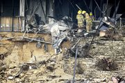 Firefighters get a close look at the damaged remains of a small aircraft, left, Friday inside a building in Austin, Texas. Joseph Stack flew his small airplane Thursday into the building that houses several offices of the Internal Revenue Service.