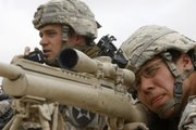 Sgt. Ryan Mack, 25, from Defiance, Ohio, left, talks on the radio as Spc. Thomas Leuthold, 20, from Hills, Minn., takes aim, as members of the 1st Battalion, 17th Infantry Regiment, 5th Brigade, 2nd Infantry Division, face Taliban insurgents during a firefight Sunday in the Badula Qulp area, west of Lashkar Gah in Helmand province, southern Afghanistan.