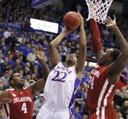 Kansas forward Marcus Morris goes up against Oklahoma defenders Tony Crocker (4) and Tiny Gallon (24) during the first half, Monday, Feb. 22, 2010 at Allen Fieldhouse.