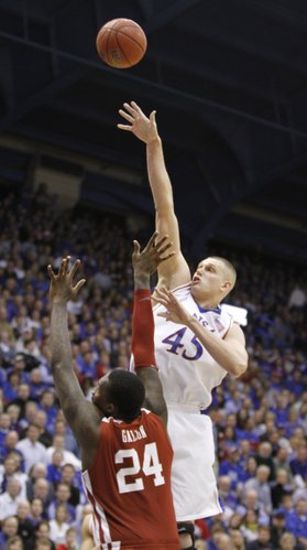 Kansas center Cole Aldrich lofts a shot over Oklahoma forward Tiny Gallon during the second half, Monday, Feb. 22, 2010 at Allen Fieldhouse.