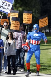 "A man dressed as ""Captain America"" joins a group of physical therapists and consumers affected by insurance premium increases, during a protest in Los Angeles on Tuesday. California lawmakers say they are astonished by a plan by Anthem Blue Cross to boost individual insurance premiums by as much as 39 percent."