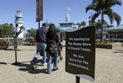 Guests pass a sign noting the Shamu Show is closed as they enter the Orlando, Fla., SeaWorld theme park Thursday, a day after an incident involving the death of a trainer.