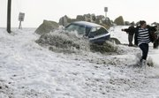 A wave breaks over an occupied car as people attempt to tow it to safety Friday at Camp Ellis in Saco, Maine. The driver left the car as the tide continued to rise, flooding local streets. A third blizzard in less than a month hit the Northeast, leaving more than a million homes and businesses without power.