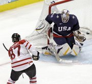 Canada's Sidney Crosby (87) shoots past USA goalie Ryan Miller (39) for the game-winning goal in the overtime period of a men's gold medal ice hockey game at the Vancouver 2010 Olympics in Vancouver, British Columbia, Sunday, Feb. 28, 2010.
