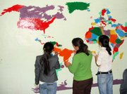 Students in Mongolia paint a world map in their geography classroom with assistance from Peace Corps volunteer Elizabeth Durkin.