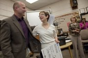 Lawrence High vocal teacher Cathy Crispino, center, was congratulated by Superintendent Rick Doll, left, after she was announced as the Lawrence Secondary Teacher of the Year Monday, Mar. 1, 2010.