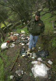 Fresno County Sheriff's Lt. Rick Ko walks through a campsite at an abandoned marijuana growing site in the Sequoia National Forest near Fresno, Calif.