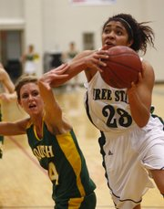 Free State's Chantay Caron (23) takes the ball strong to the hoop, drawing a foul on SM South's Rebecca Dunn (4) and making the shot during the fourth quarter of the game on Wednesday, March 3, 2010, at FSHS.