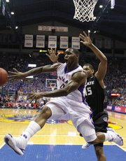 Kansas guard Sherron Collins whips a pass around Kansas State center Luis Colon during the first half Wednesday, March 3, 2010 at Allen Fieldhouse.