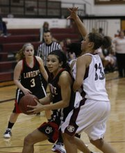 Lawrence High School's Jasmyn Turner (5) works past Shawnee Mission North defender Brianna Kulas (33) for a layup. The Lions saw their season end 54-42 Wednesday, March 3, 2010.