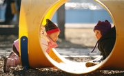 Madilynn Prewitt, left, and Joy Malin meet inside a playground tube at Hilltop Child Development Center.