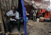 Antoine Laguerne reads a bible in the doorway of his makeshift tent at a camp for earthquake survivors Friday in the Petionville Golf Club, Haiti. The 7.0-magnitude earthquake hit Haiti on Jan. 12 leaving more than a million people living in makeshift camps.
