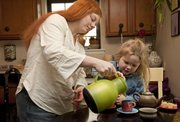 "Cami Kennedy and her daughter Suzana, 3, fill their cups for tea time recently in their Lawrence home. ""I don't purposely give her any caffeine,"" says the Lawrence mom, who treats her daughter to noncaffeinated children's tea. ""You're 100 percent supplying what they take in, so I just feel more responsible for keeping her away from things that aren't necessary."""