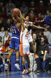 KU's Carolyn Davis (21) goes up against Oklahoma State's Desiree Jefferies (32) and LaSharra Riley (21)  Thursday night March 11, 2010 in Municipal Auditorium with KU losing 76-69.