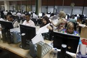 Counting and data input workers calculate election data at the Independent High Electoral Commission on Thursday in Baghdad. The partial preliminary results from four of 18 provinces in Iraq show the prime minister's bloc and a secular challenger winning two provinces each.