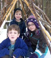 Simon Ruland, 7, Max Ruland, 3, and Jadelin McLeod, 7, sit inside a stick teepee, one of several natural play spaces in the Rulands' yard.