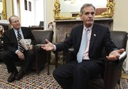 Sen. Judd Gregg, R-N.H., right, accompanied by Sen. Lamar Alexander, R-Tenn., gestures during a health care news conference Thursday on Capitol Hill in Washington.